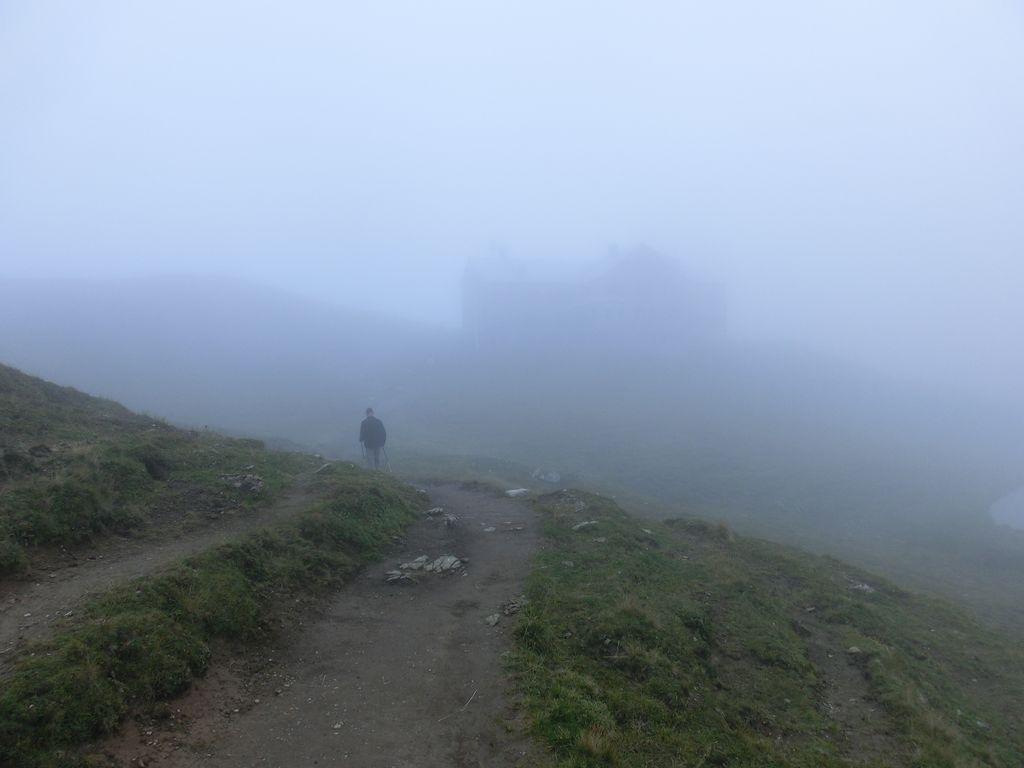 Der Abstieg vom Rappenseekopf, die Rappenseehütte taucht im Nebel auf.
